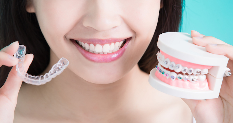 girl holding both an invisalign aligner and a metal brace