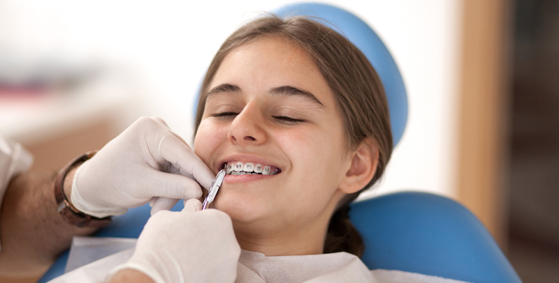 young girl in a dental chair having her braces taken off