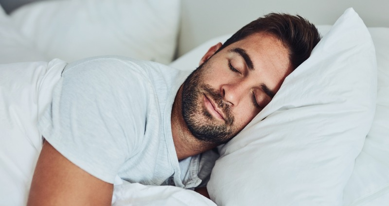 A man getting a good nights sleep after fixing sleep problems with adult orthodontics
