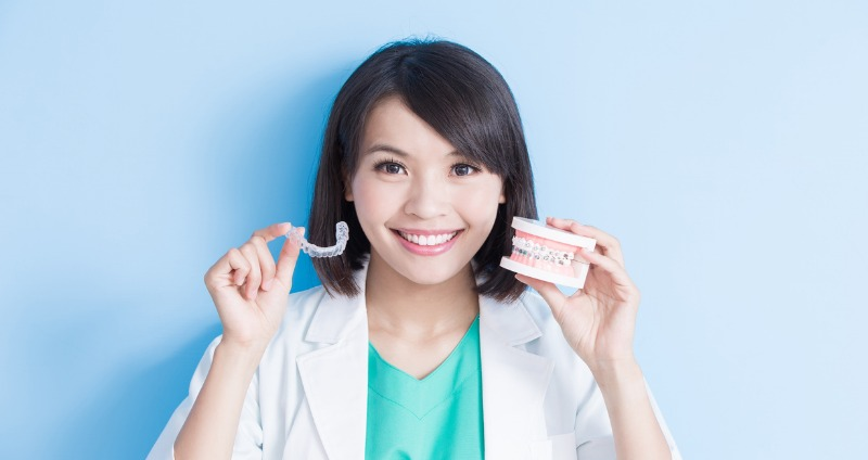 Female orthodontist holding an Invisalign aligner and jaw mould with braces