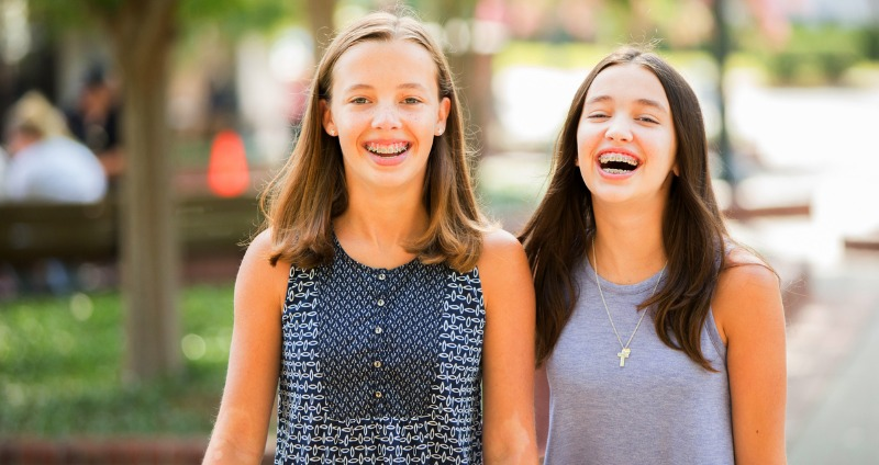 Two female teenagers with orthodontic braces smiling and laughing