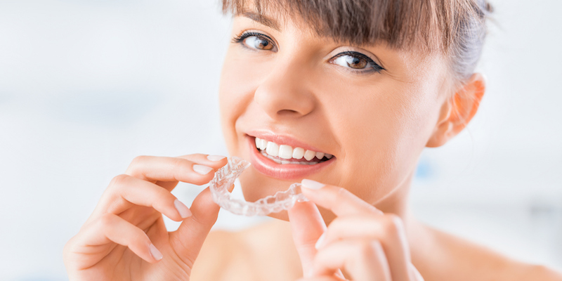 young woman holding an invisalign aligner