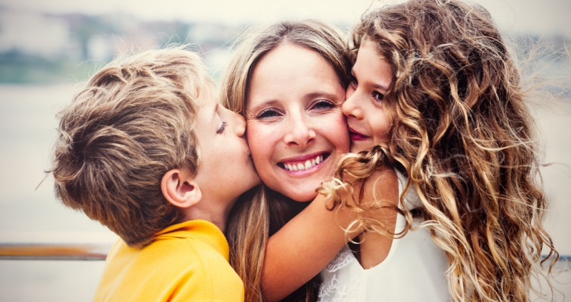 a happy mother with her young son and daughter smiling thinking about early orthodontic treatment