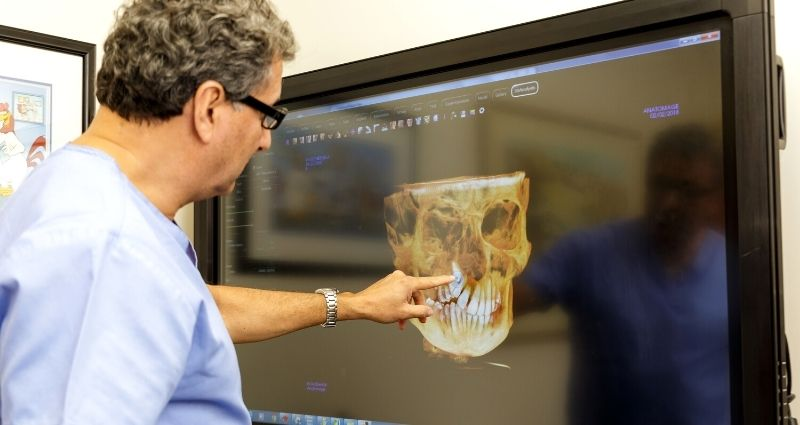 Dr Mithran Goonewardene reviewing a 3D scan of patients jaw on TV screen.