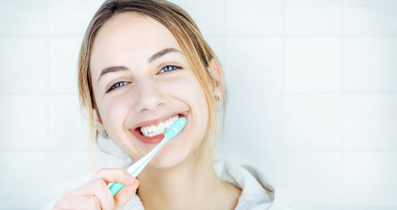 Young teenage girl smiling brushing her teeth properly