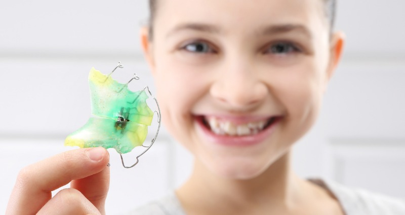a young girl holding her orthodontist plate and smiling