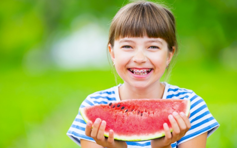 young girl with dental braces holding watermelon and smiling