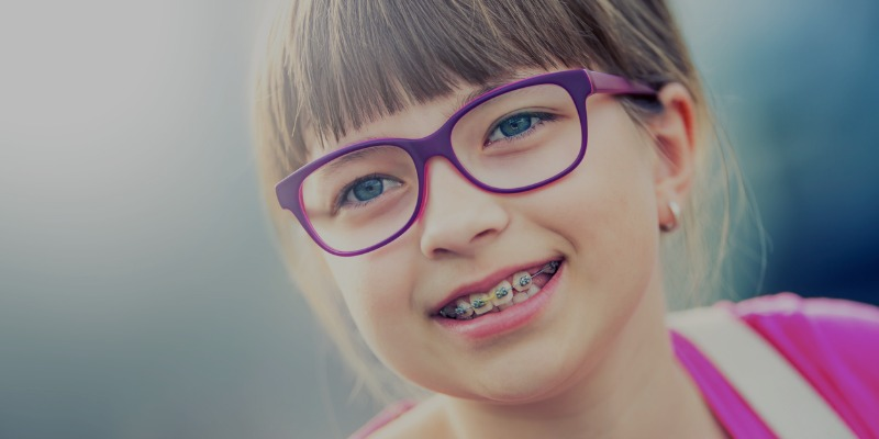 Young girl with braces and purple glasses