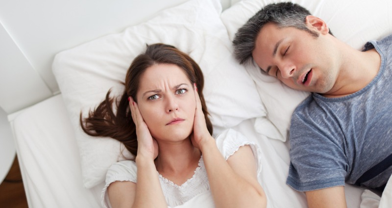 Lady laying in bed blocking her ears from snoring partner