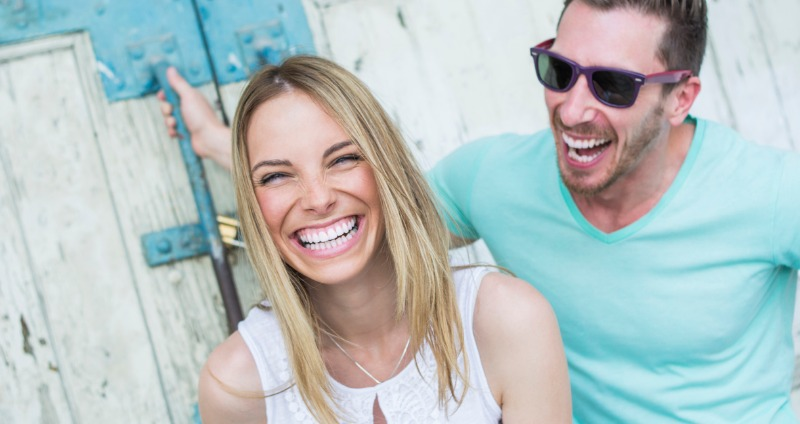 Smiling couple with straight teeth after Invisalign treatment