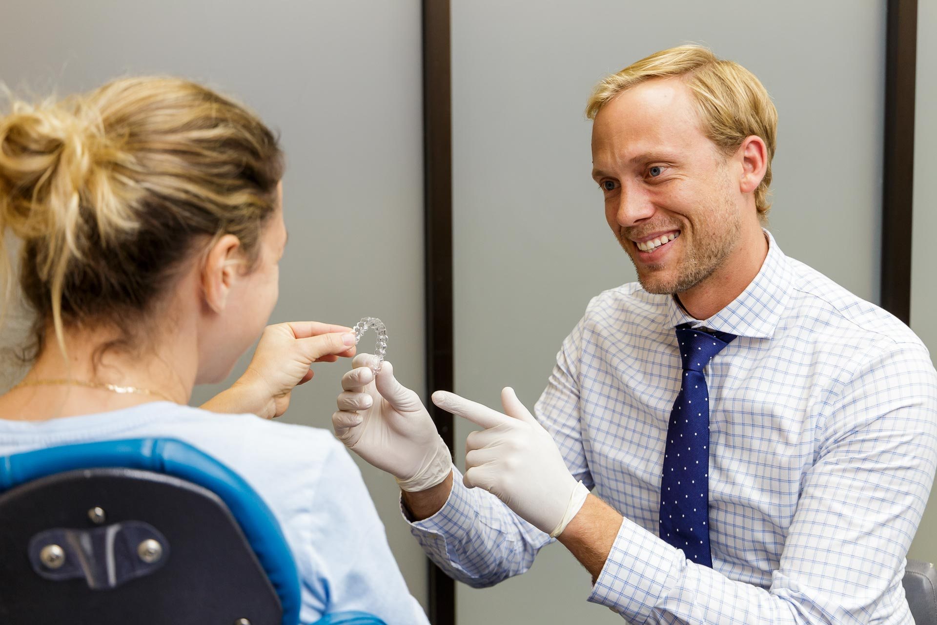 An orthodontist showing a patient their Invisalign clear retainer